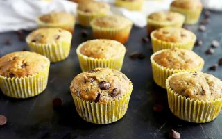 Horizontal image of a banana muffins with chocolate chips on a black surface