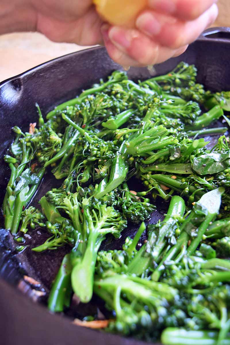 Vertical image of a hand squeezing fresh lemon juice onto a large frying pan of broccoli rabe.