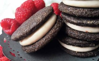 Horizontal image of a stack of cookies, and one other cookie resting on the stack, surrounded by raspberries.