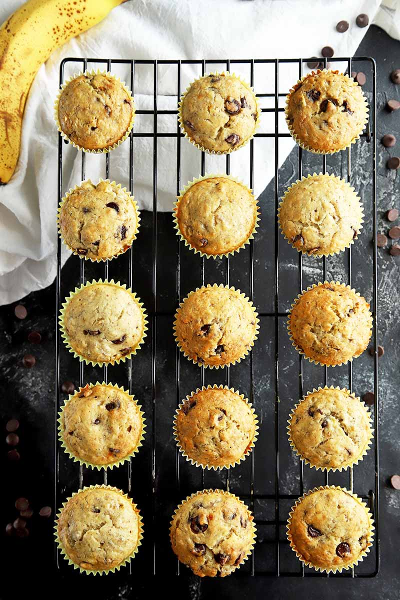Vertical top-down image of a cooling rack with neatly placed rows of banana chocolate chip muffins.