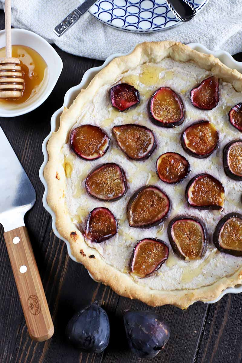 Vertical closely cropped overhead image of a ricotta and fig tart with a pie server, fresh fruit, honey with a wooden dipper, and a small stack of plates and forks on a white cloth, on a brown wood table.