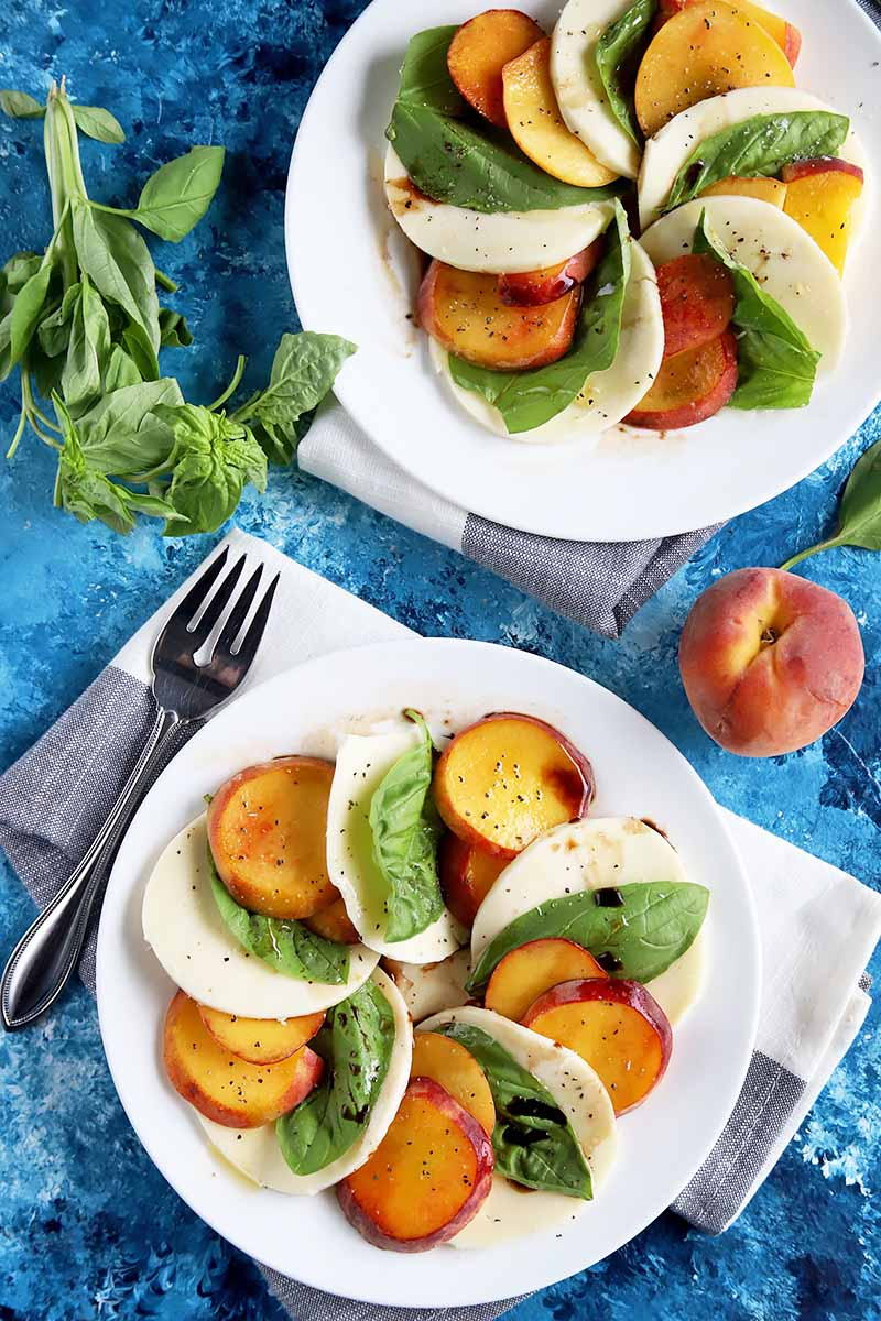 Vertical top-down image of two white plates of a shingled peach caprese dish, next to a whole peach, a fork, and basil.