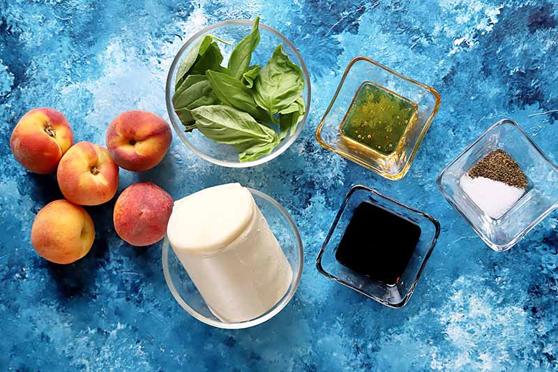 Horizontal image of various ingredients to make a fruit caprese salad on a blue surface.