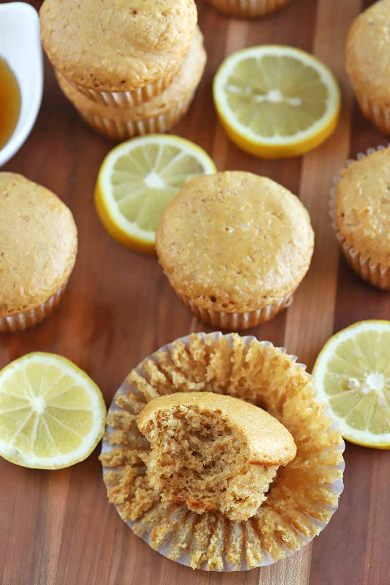 Oblique overhead horizontal image of muffins and lemon slices on a wood surface, with the one in the foreground resting on its paper wrapper with a piece missing to expose the crumb, and a small white dish of honey at the top left of the frame.