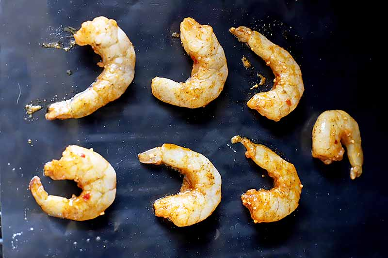 Horizontal image of grilling shrimp on a flat top.