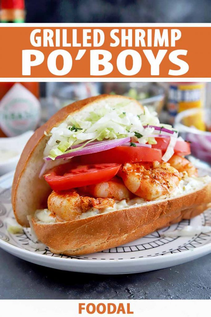 Vertical image of a shrimp sandwich with lettuce, tomatoes, and red onions with text on the top and bottom of the image.