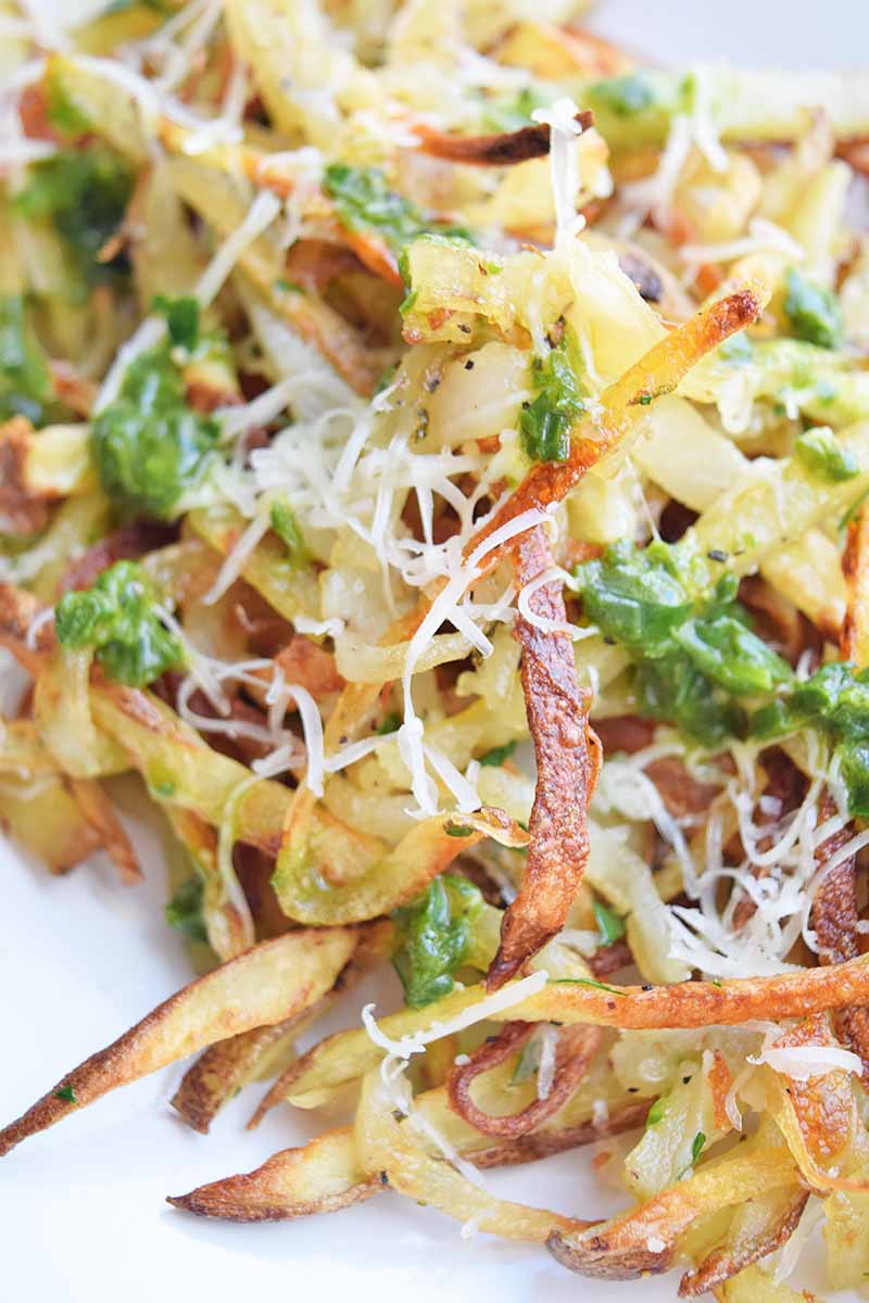 Vertical close-up image of a pile of french fries covered in green dressing and shredded cheese.