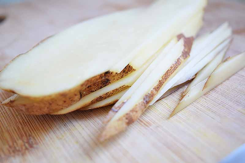 Horizontal image of thinly sliced and matchstick-sliced potatoes.