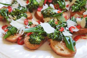 Horizontal image of a white platter of broccoli rabe tartines with sliced red chili and shaved hard cheese.