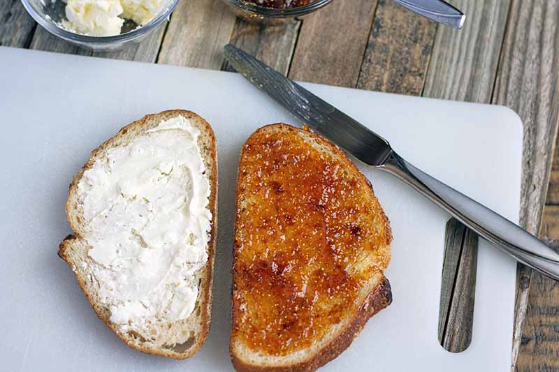 Horizontal overhead image of two slices of bread on a white plastic cutting board. One is spread with a butter and crumbled goat cheese mixture, the other is spread with fig jam. With a butter knife at the top right, and two small glass bowls of ingredients just visible at the top of the frame, on an unfinished wood surface.