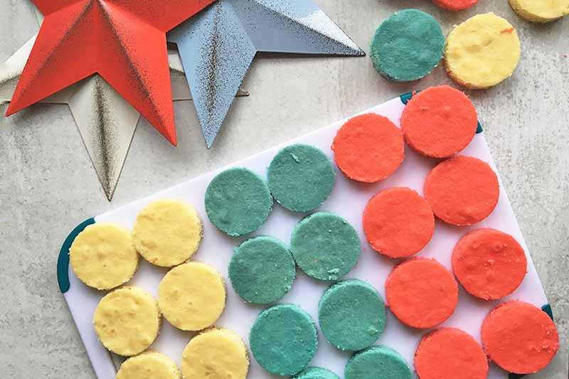 Horizontal image of cut-out circles of red, white, and blue cakes on a cutting board.