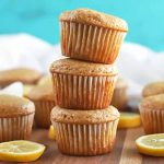 Horizontal image of a stack of three muffins surrounded by several more, with scattered lemon slices on a brown surface, with a white cloth in the background, against a sky blue backdrop.