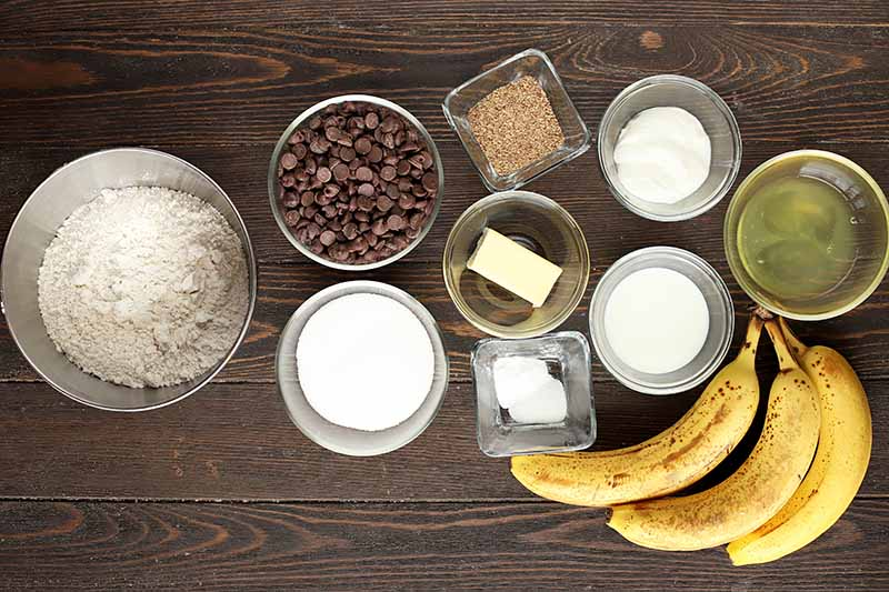 Horizontal image of assorted ingredients to make banana chocolate chip muffins.