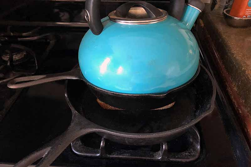 A blue kettle is on top of a small cast iron pan being used as a weight to press down on the sandwich that is in a larger cast iron pan at the bottom, on a gas stove.