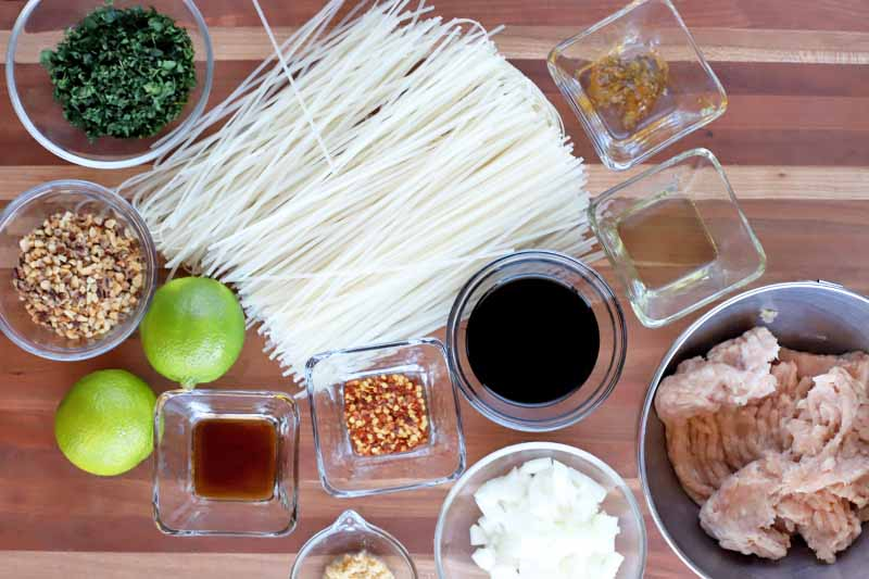 Overhead horizontal image of a pile of rice noodles and two whole limes with small glass and stainless steel bowls of chopped cilantro, crushed peanuts, soy sauce, chopped onion, ground chicken, garlic, tamarind paste, fish sauce, and oil, on a striped light brown and beige wood surface.