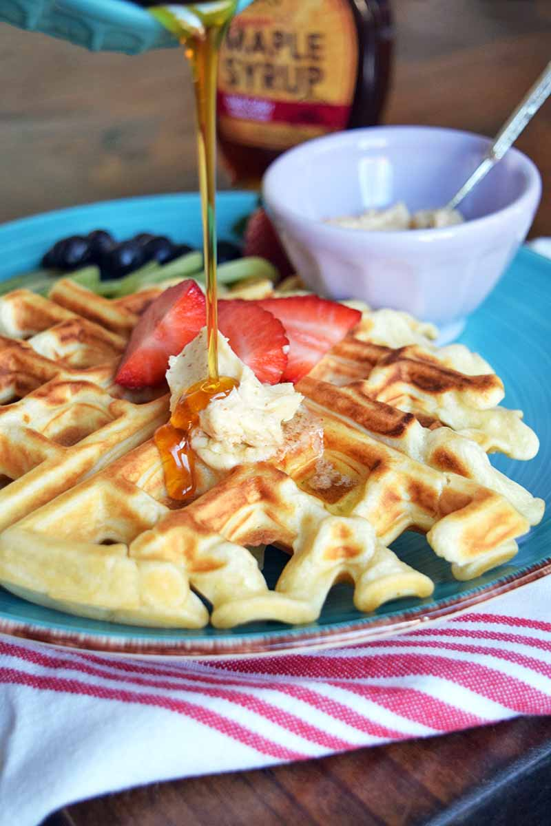 Vertical image of syrup being poured over a fluffy waffle with garnishes on a blue plate next to a white bowl with butter.