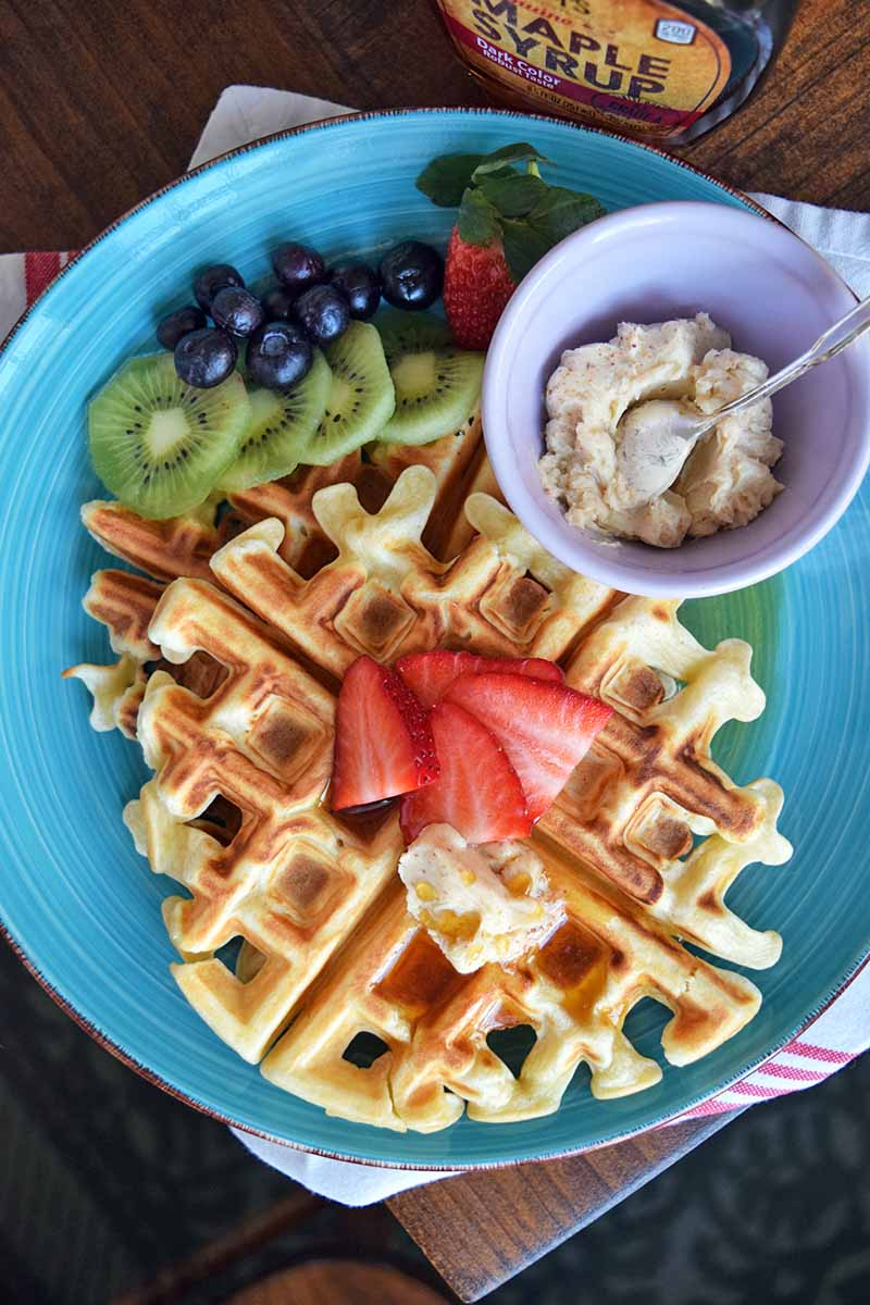 Vertical top-down image of a blue plate with two waffles, fresh fruit, and butter.