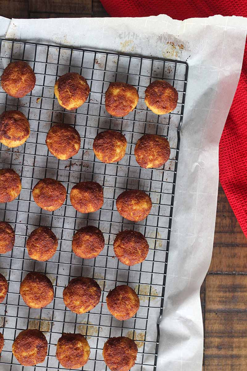 Vertical closely cropped overhead image of a wire cooling rack with cinnamon cookies arranged in rows on top, on top of a piece of white parchment paper, with a red cloth kitchen towel to the right, on a brown wood surface.
