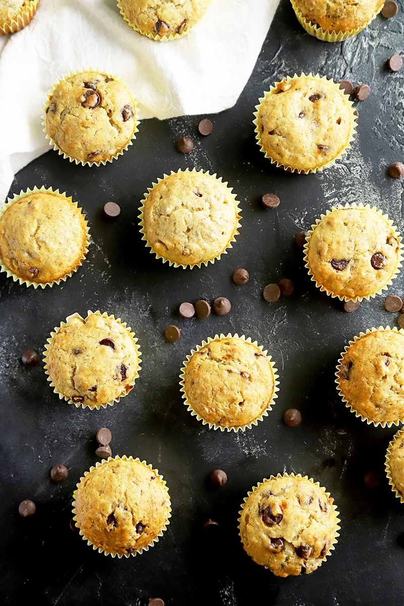 Vertical top-down image of muffins studded with chocolate chips on a black slate.
