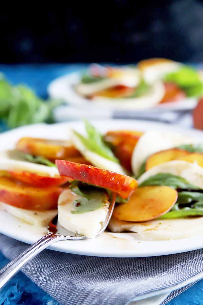 Vertical image of a fork with pieces of a peach caprese salad on a white plate.