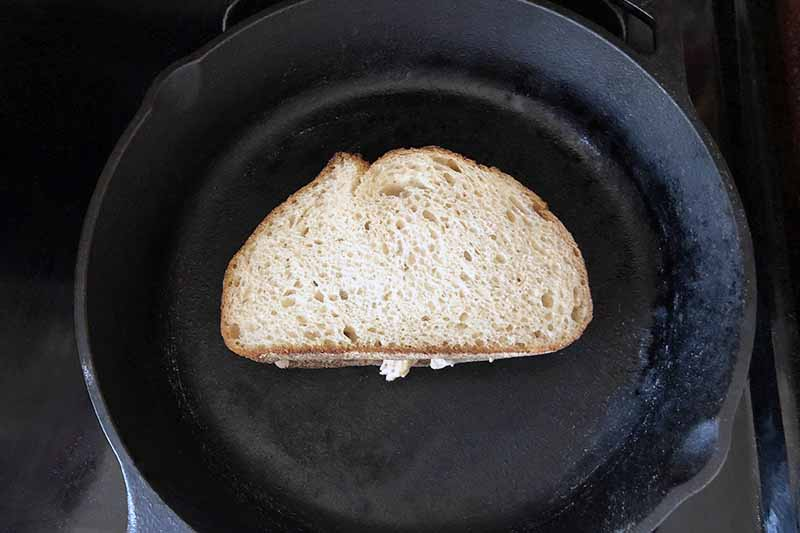Overhead horizontal image of a cast iron pan on a black stove, with a piece of buttered bread at the center of the pan.