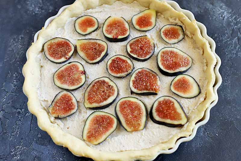 Horizontal overhead image of a tart in a ceramic pan that's ready to bake, with ricotta filling and sliced fresh figs on top, on a mottled gray background.