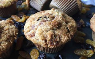Horizontal image of scattered muffins on a slate surrounded by dried fruit.