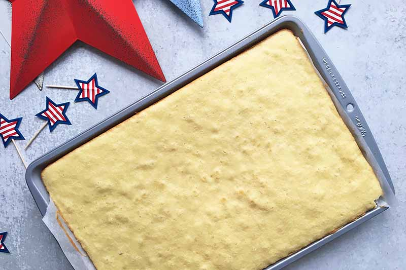 Horizontal image of a sheet pan with a baked vanilla cake surrounded by star decorations.