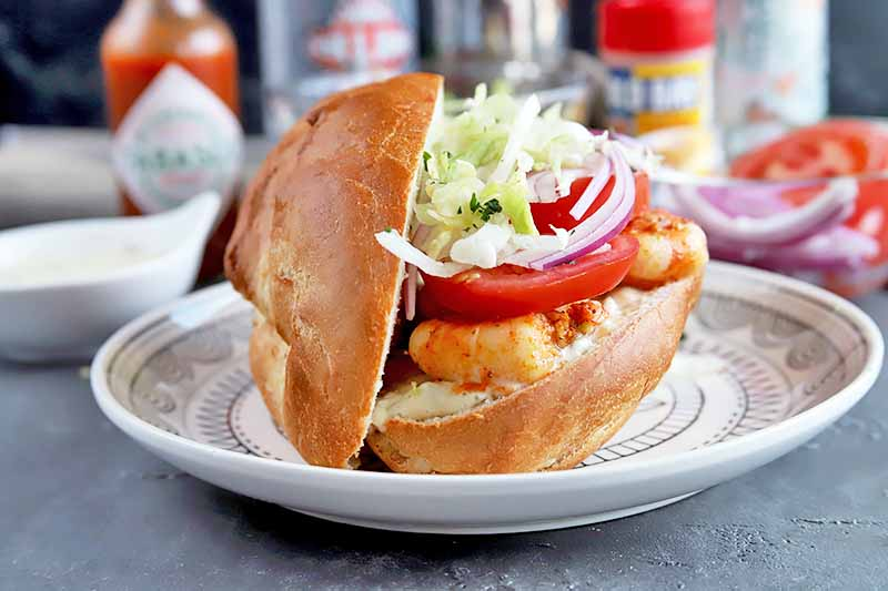Horizontal image of a whole seafood sandwich with shrimp, lettuce, onion, and tomato.