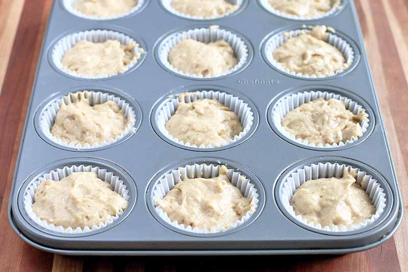 Vertical image of a muffin tin with paper liners filled with batter, on a striped beige and brown wood surface.