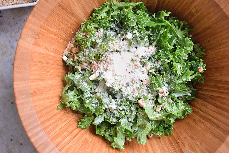 Horizontal closely cropped overhead image of torn kale in the bottom of a wooden bowl topped with a pile of grated Pecorino cheese, on a gray surface.