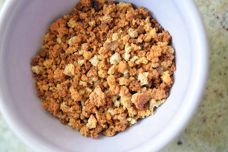 Horizontal overhead image of coarse toasted breadcrumbs in a white ceramic bowl, on a speckled gray surface.