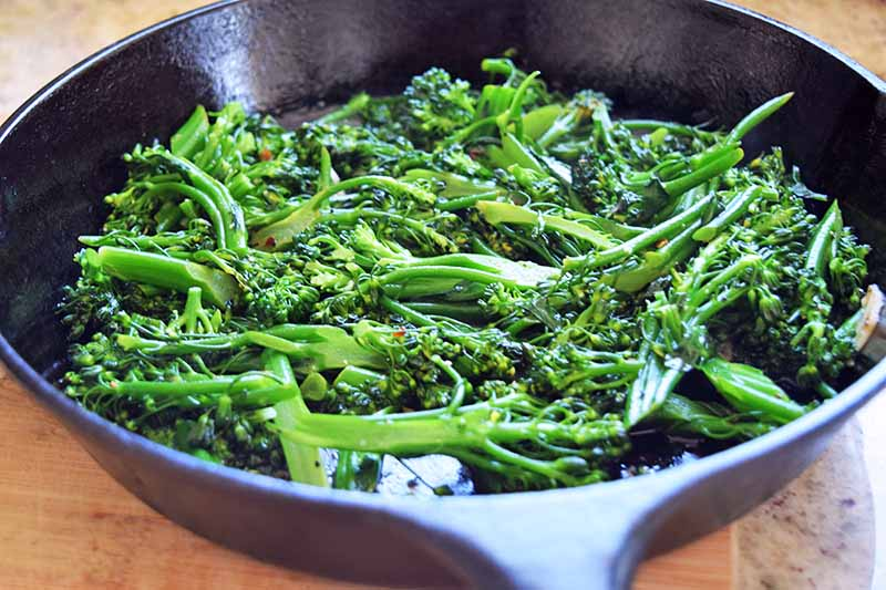 Chopped broccoli rabe in a large cast iron frying pan on a brown countertop.