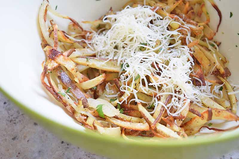 Horizontal image of a bowl of cooked potato matchsticks with a pile of cheese on top.
