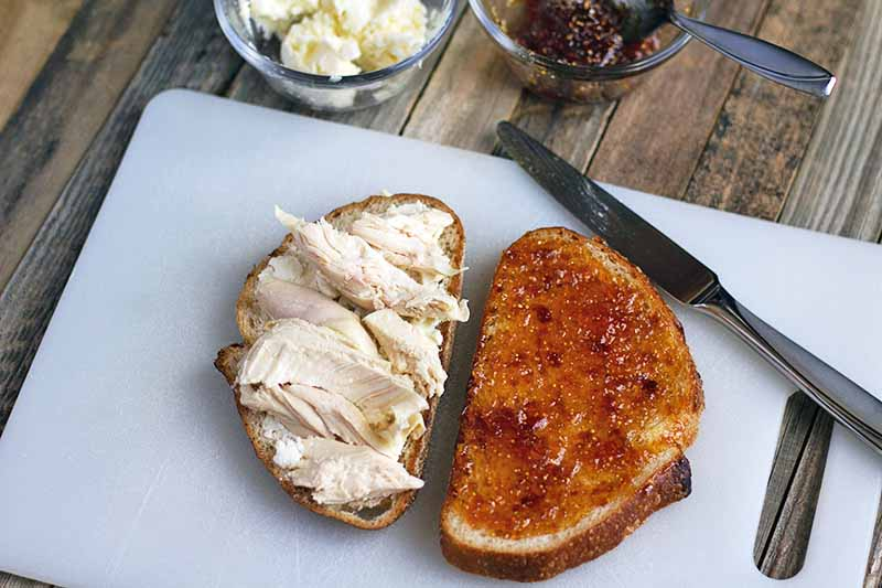 Horizontal image of two slices of bread on a white plastic cutting board, one with pieces of roasted chicken breast meat on top on the left, the other spread with jam on the right, with a knife and two small glass bowls of a butter and goat cheese mixture and jam in the background, on an unfinished wood surface.