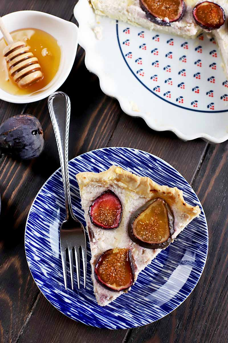 Vertical overhead image of a slice of fig and ricotta tart on a blue plate with a fork, with a few pieces of the fresh fruit on a brown wood surface beside a small white bowl of honey with a wooden dipper, and a patterned white ceramic pan filled with the rest of the dessert.