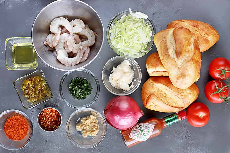 Horizontal top-down image of assorted ingredients in bowls with seafood and bread buns.