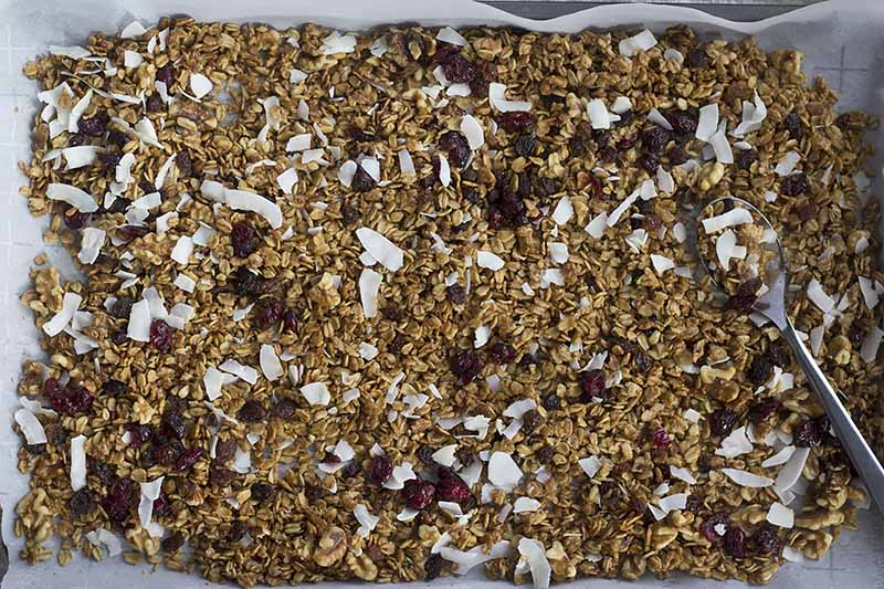 Horizontal image of granola with dried fruits, nuts, and coconut on a sheet pan.