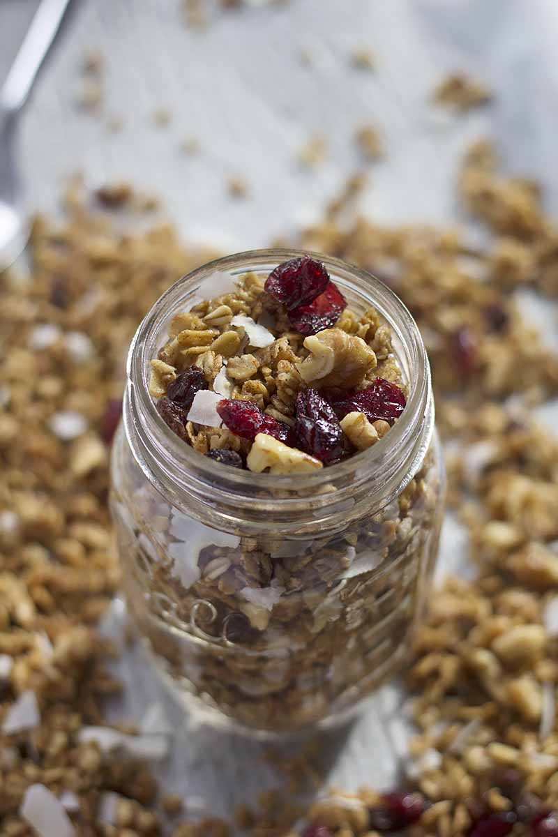 Vertical image of a glass mason jar filled with granola with dried fruits and nuts.