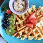 Horizontal image of a blue plate with waffles and fresh fruit.