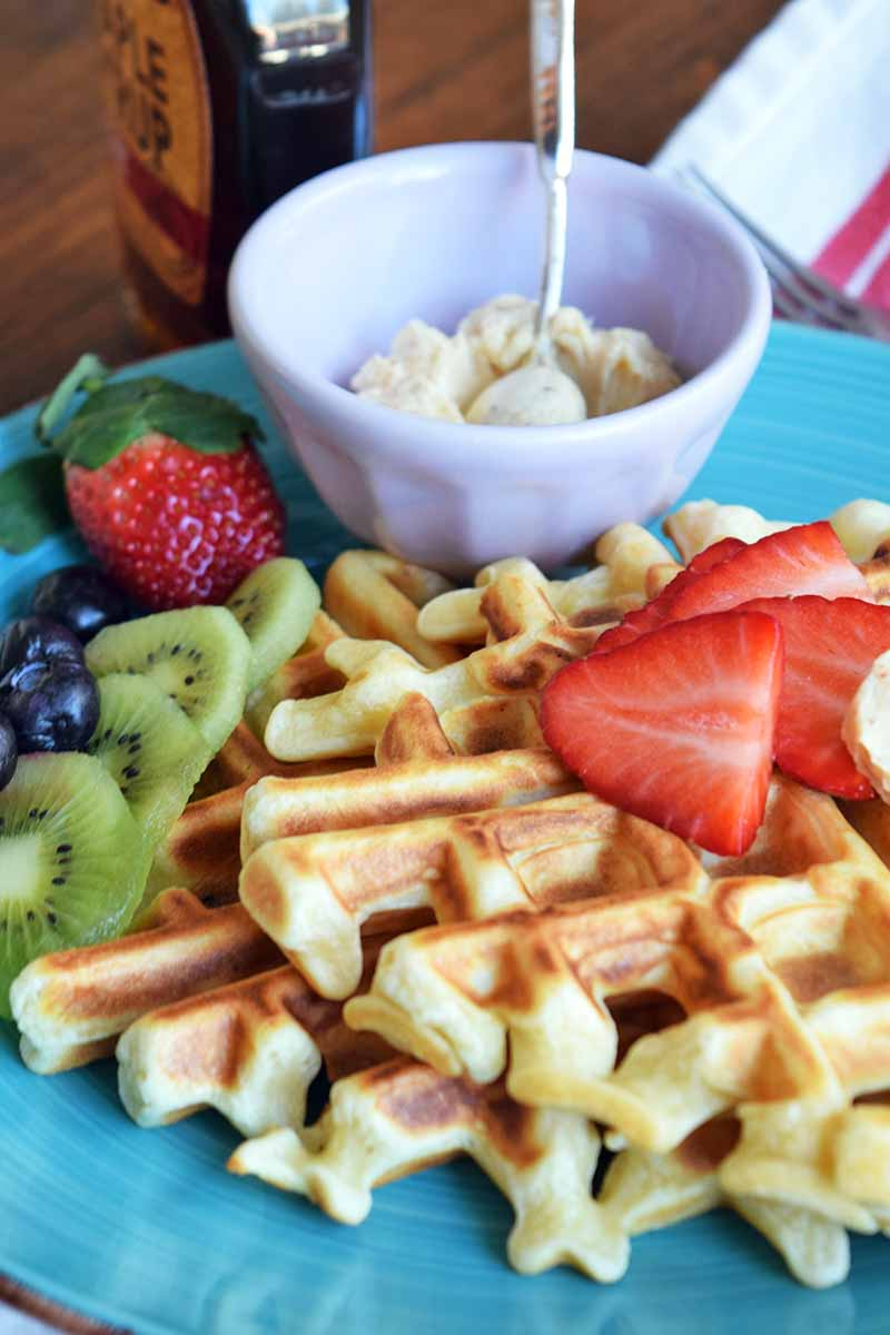 Vertical image of two stacked waffles with fresh fruit and butter on a blue plate.