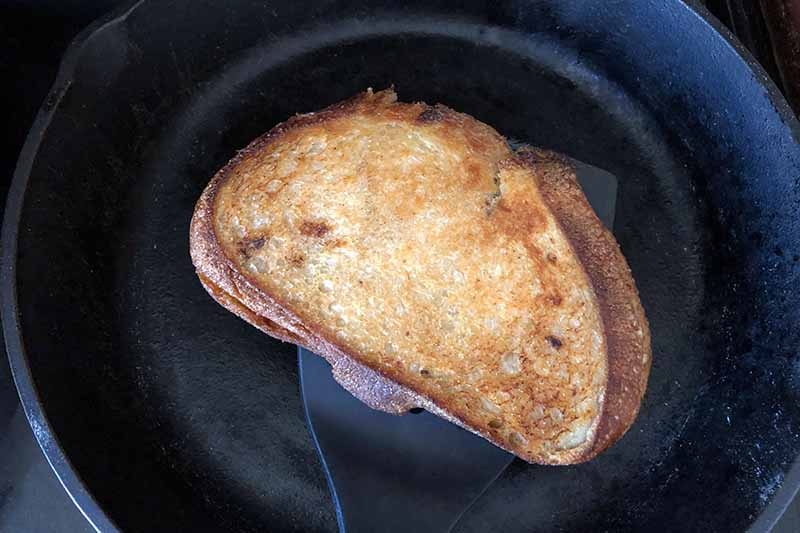 Horizontal overhead image of a grilled sandwich made with sourdough bread that is golden brown, in a cast iron pan.