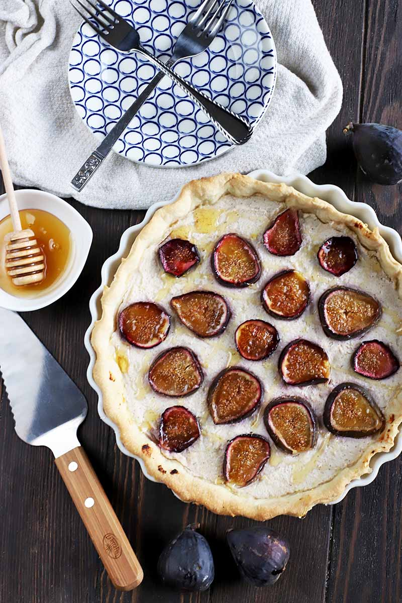 Vertical overhead image of a ricotta tart topped with fresh figs, with a wood and metal pie server, a small white bowl of honey with a wooden dipper, a small stack of plates and forks, and some of the fresh fruit scattered around the other items, on a dark brown wood table.