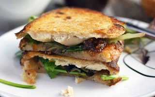 Horizontal image of two golden brown toasted halves of a sandwich with salad greens, fig jam, goat cheese, and chicken, on a white plate.