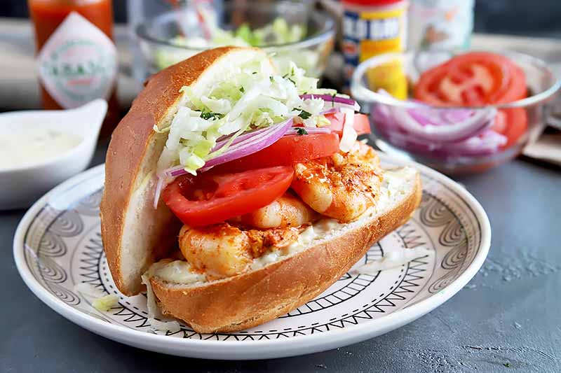 Horizontal image of a whole grilled shrimp po'boy with shredded lettuce, onions, and tomatoes with all of the ingredients in the background.