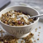 Horizontal image of a bowl of dried fruit and coconut granola with a metal spoon.