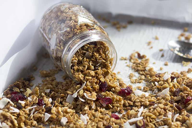 Horizontal image of a mason jar tipped over and pouring out granola.