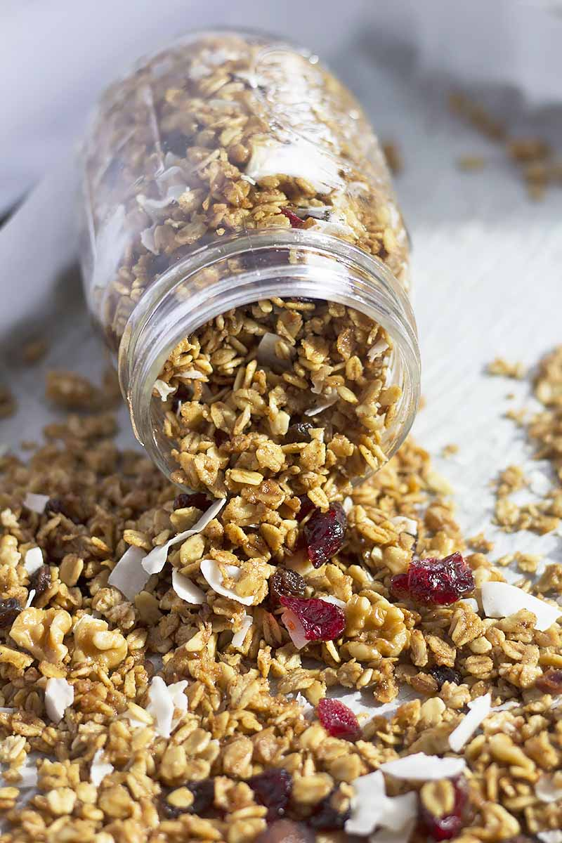 Vertical image of a mason jar with granola spilling over on a white surface.
