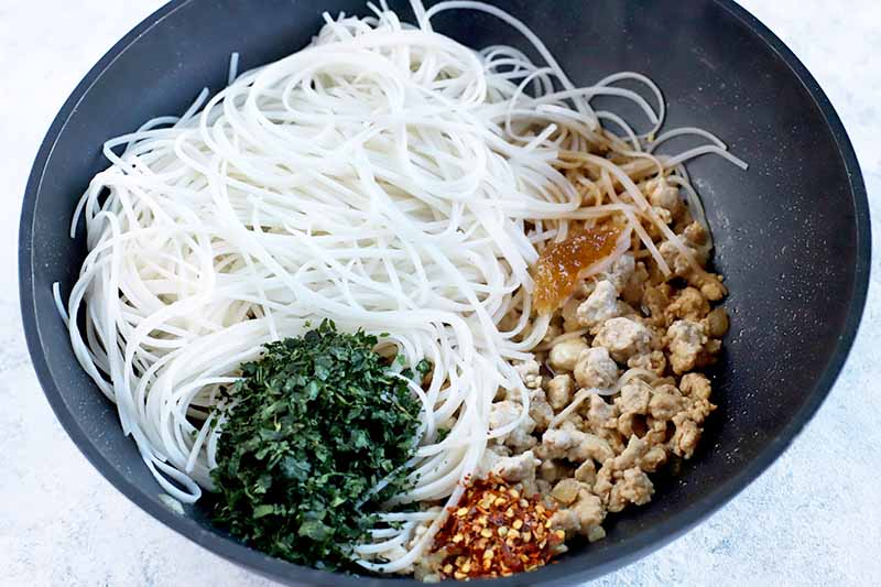 A nest of rice noodles with a small pile of chopped cilantro, red pepper flakes,and cooked ground chicken in a black metal wok, on a speckled light blue and white surface.