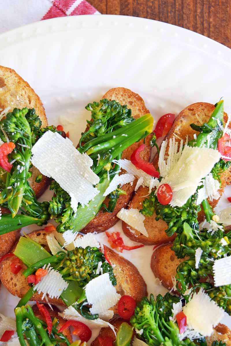 Vertical overhead closely cropped image of a white ceramic platter of baguette toast rounds topped with broccoli rabe, thinly sliced red chilies, and shaved hard cheese, on a brown wood surface with a white and red striped cloth.